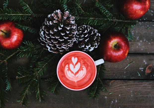 Red latte with leafy coffee art in a white ceramic mug. The flatlay is decorated with pinecones, red apples, and Christmas tree branches.