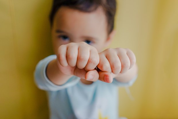 A baby against a yellow backdrop with their fists outstretched.