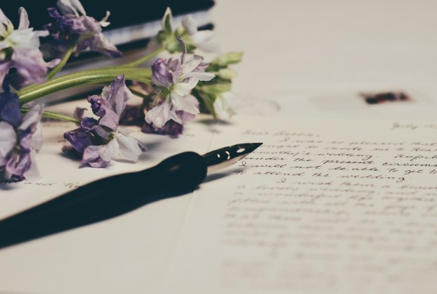 A faded picture of a fountain resting over a handwritten letter. Purple flowers lay on the top left of the table.