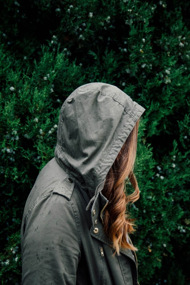 Side profile of someone with long, curled hair in a grey utility raincoat. Their hood is pulled up. Green foliage covers the background.
