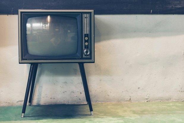 A retro TV against a concrete background.