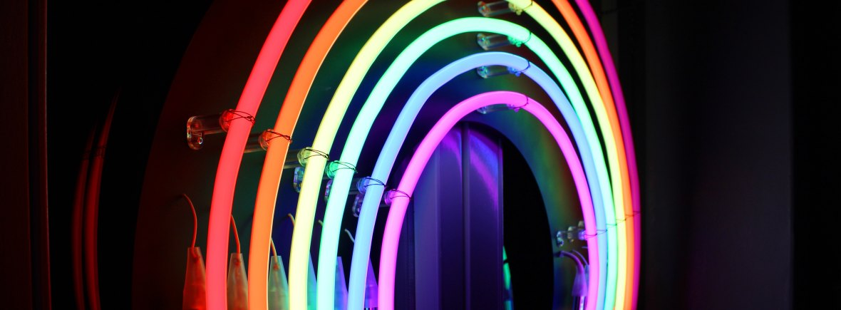 A side profile of a neon rainbow sign against a dark background.
