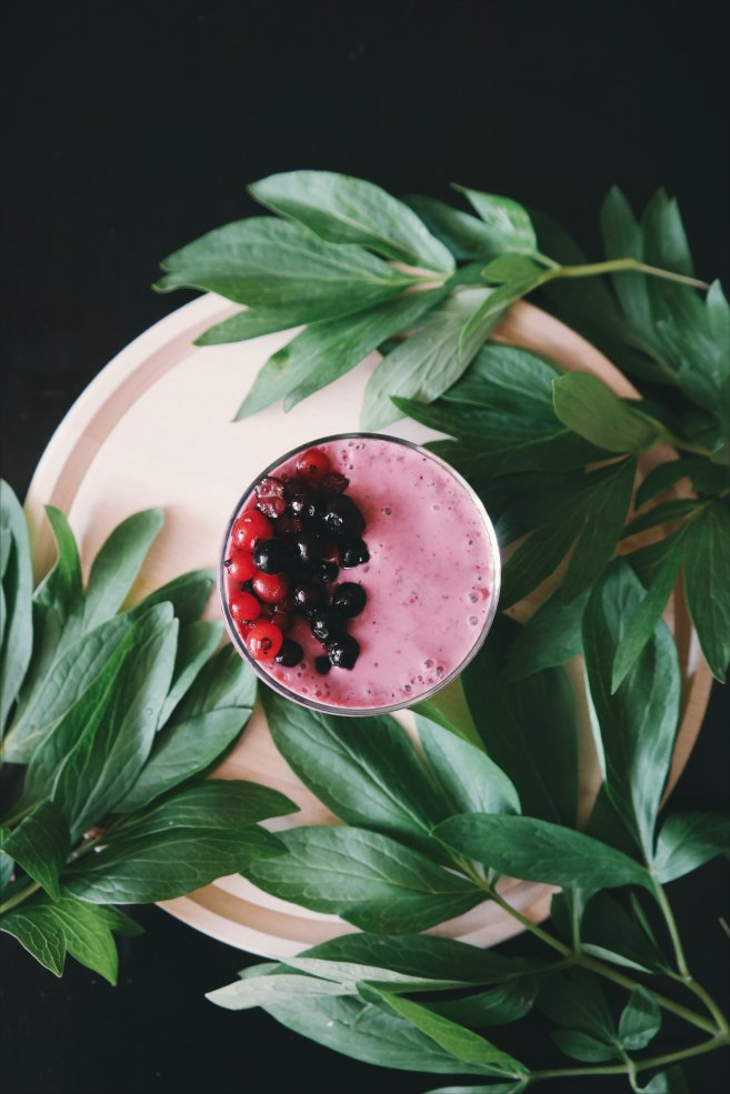 Flatlay of a pink smoothie with berries on top. Green foliage branches are scattered around it.