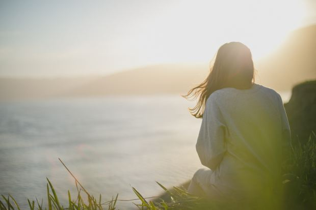 Photo of a woman sitting on a hilltop, looking out at the ocean's horizon. The sun highlights her silhouette, like a small miracle.