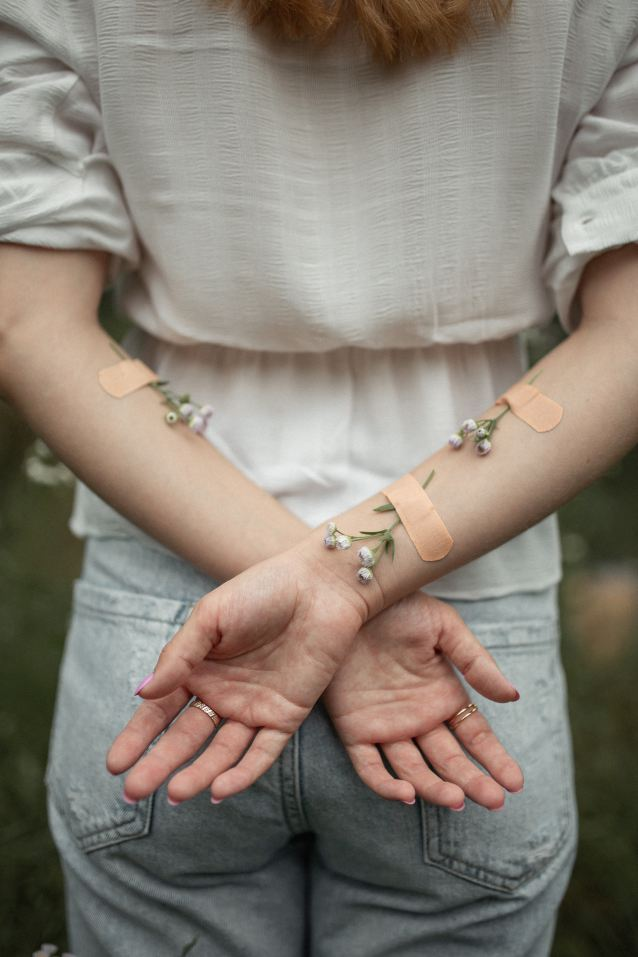 The back of a femme person. Their arms are crossed behind their back, with tiny white flowers attached to look like veins. Bandaids hold them in place.